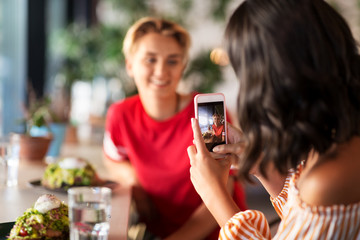 leisure, technology and people concept - female friends having lunch and photographing by smartphone at restaurant or cafe