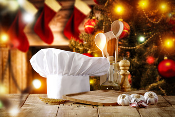 Cook hat on table and christmas tree with fireplace
