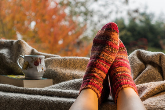 Woman's feet wearing handmade knitted colorful wool socks next to a hot cup of tea in a cozy decor. Keeping warm on a cold day concept.