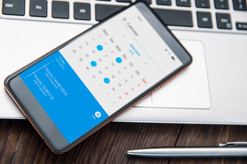 Smartphone witch notch lies on the desk with calendar application that remind about invoices to pay. Application on screen created in graphic program