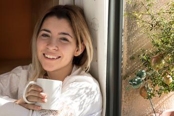 Woman drinking coffee near a window