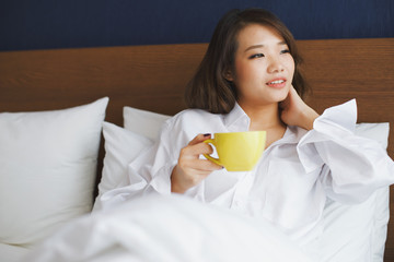 Coffee morning on bed, young asian woman holding cup of hot coffee or tea in the bedroom, focusing on yellow cup