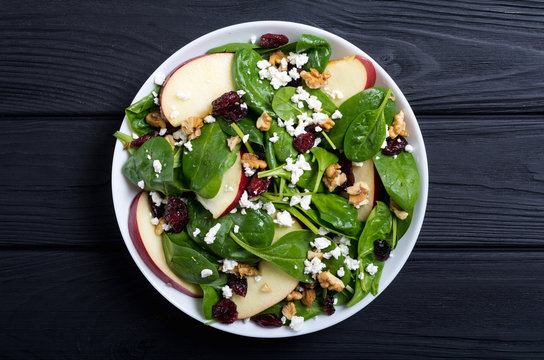Autumn spinach salad with apple , cheese , walnut and dried cranberry . Healthy vegetarian food