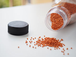 Fish feed Small pellets In a clear plastic bottle with a lid on a white background.