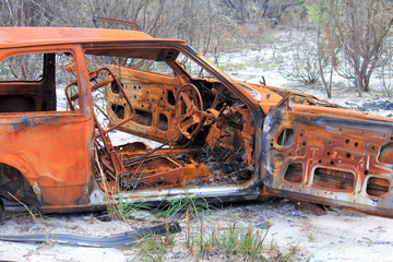 Rusted, burnt out car body that has been abandoned