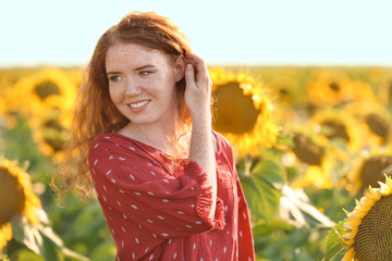 Beautiful redhead woman in sunflower field on sunny day