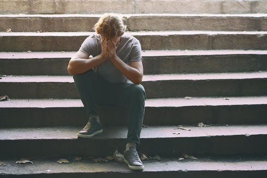 Stressed young man sitting on stairs outdoors