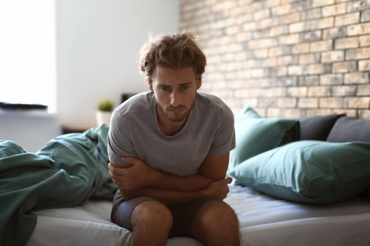 Depressed young man sitting on bed