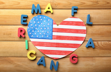 Heart shaped drawing of American national flag with color letters on wooden table