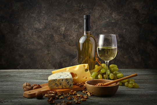Glass and bottle of white wine with snacks and ripe grapes on wooden table