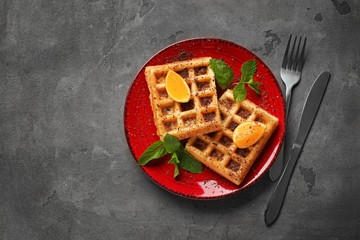 Tasty waffles with cut orange on plate