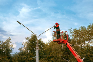 Municipal worker with helmet and safety protective equipment installs new diode led lights. Worker in lift bucket repair street light pole. Modernization of street lamps. Technician on aerial device
