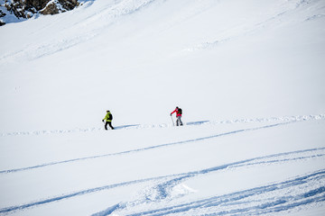 Image from afar of two sporty skiers in snowy resort