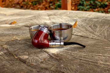 e-pipe with blurred background and cup of coffee in natural ambient. Electronic cigarette, electronic pipe, personal vaporizer, vaping device..