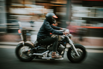 Blurry motion of man riding a motorcycle in the street.