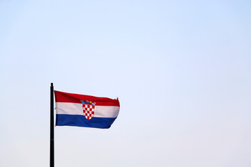 Flag of Croatia, blowing in the wind. Sky in the background, selective focus.