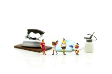 Miniature people : Maid,woman housewife ironing clothes iron in laundry at home.