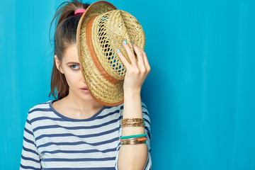 Portrait of beautiful girl holding straw hat near face.