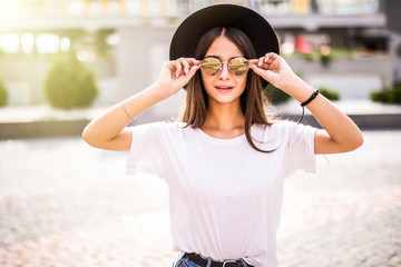 Beautiful young woman in hat and sunglasses walking in the city. Fashion.