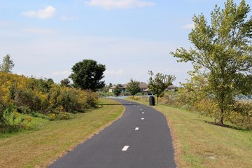 The blacktop pavement pathway in the park on sunny day.