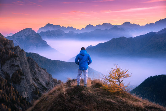 Sporty man on the mountain peak looking on mountain valley with low clouds at colorful sunset in autumn in Dolomites. Landscape with traveler, foggy hills, forest in fall, amazing sky at dusk in Alps