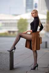 Girl with perfect legs in pantyhose at the city square.