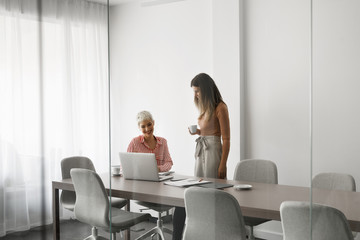 Two beautiful smiling businesswomen working together at meeting room.