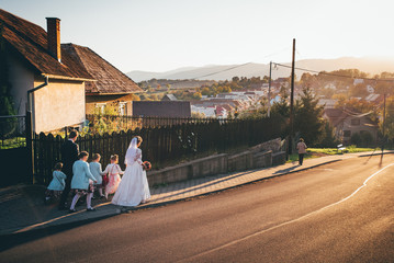 Bride groom and young bridesmaids walking in sunny village