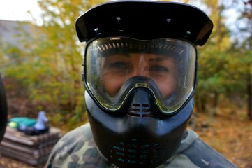 Girl in camouflage and paintball mask