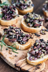 Homemade mixed Olive Tapenade made with garlic, capers, olive oil, Kalamata, black and green olives spread over toasted bread. Selective focus on center canape with blurred background.