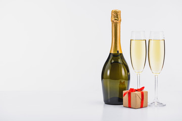 close up view of bottle and glasses of champagne with wrapped gift on white background