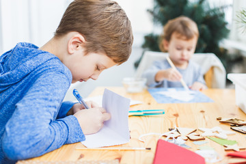 Boy and little girl preparing christmas cards for grandparents.