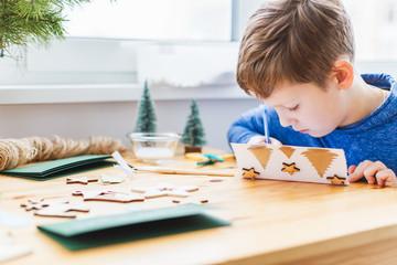 Adorable boy preparing christmas cards for grandparents.