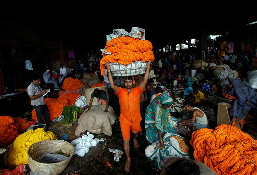 A labourer carries garlands of marigold flowers to supply at a wholesale flower market, which will be used to decorate temples and homes, on the eve of Diwali