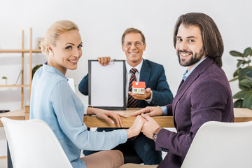 happy couple holding hands while insurance agent showing contract and small house