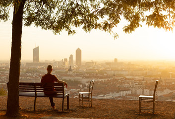 Man on a bench enjoying the summer sunrise over a city. Lyon, France.