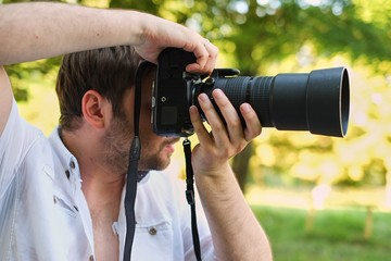 happy young man holding digital camera with big lens taking picture on city street