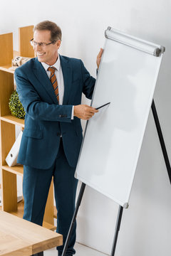 adult businessman pointing at white board at meeting in office