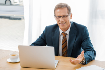adult smiling man in glasses sitting at table with laptop in insurance office