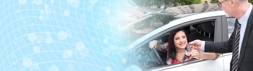 Car salesman giving car keys to young woman