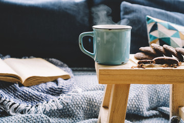 Cup of hot drink on wooden table. Living room interior with blue sofa on background. Cozy winter or autumn concept