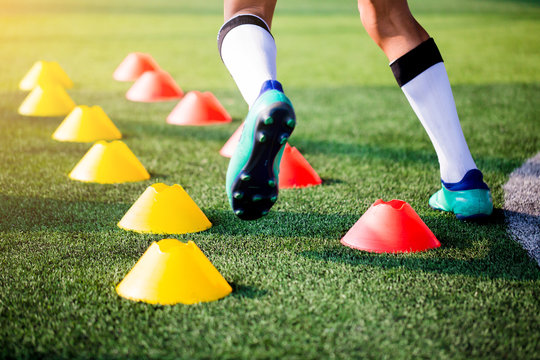 Football player Jogging and jump between cone markers on green artificial turf for football training.
