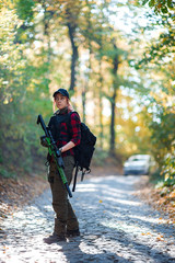Woman with rifle in the forest. Car in the background/Red-haired young woman with a rifle on the road in the forest. Car in the background