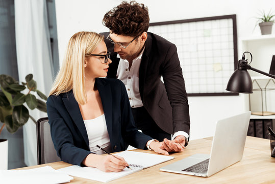 young businesspeople holding hands while flirting in office, office romance concept