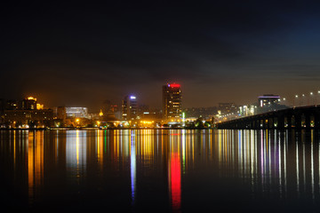 Panoramic view of the city at night. Cityscape near the river at night with reflection in the water.