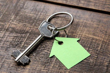 The concept of buying a home. Keys with keychain house on a brown wooden background close-up.