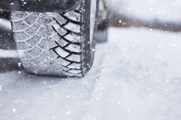 Car is on a snow-covered winter road.  Сlose up of winter tires