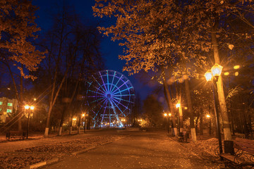 Evening autumn alley with a luminous observation wheel in the city of Ivanovo.