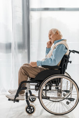 thoughtful sad senior man sitting in wheelchair in nursing home