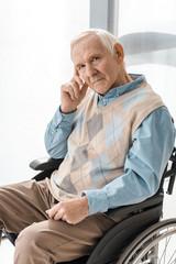 thoughtful sad senior man sitting in wheelchair in nursing home